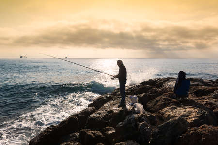 A fisherman standing with the fishing rod in his hand, he is on the rocks at sunset, near him buckets and equipment in bags, on the bottom an oil tanker sails on the horizon, the sky is cloudy and golden.