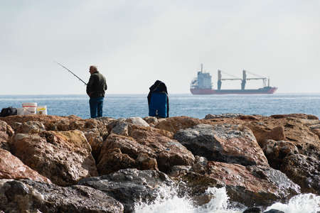 A fisherman standing with the fishing rod in his hand, he is on the rocks while he watches around him, near him buckets and equipment in the bags, on the bottom an oil tanker sails on the horizon.