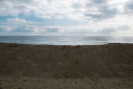 Dune di sabbia erette per proteggere gli edifici costruiti vicino alla spiaggia, il cielo è nuvoloso, sopra il mucchio di sabbia c'è l'orizzonte sul mare