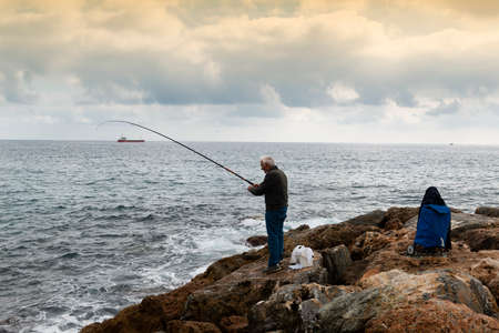 A fisherman standing with the fishing rod curved in his hand, he is on the rocks while trying to recover a fish, on the bottom an oil tanker sails on the horizon, the sky is cloudy