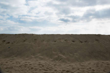Sand dunes erected to protect buildings built near the beach, the sky is cloudy