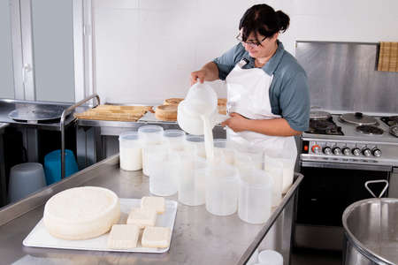 Cheesemaker pours the curdled milk into plastic forms to shape the cheese