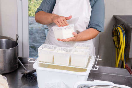 Cheesemaker turns fresh cheese into plastic containers