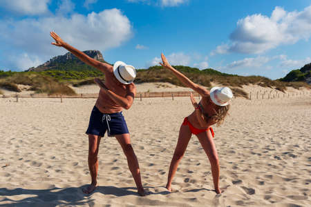 Couple in hat and sun glasses on the beach of Cala Mesquida Mallorca Spain, makes the dab gesture