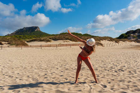 woman in hat and sun glasses on the beach of Cala Mesquida Mallorca Spain, makes the dab gesture