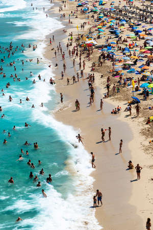 Mallorca, Spain, August 16, 2019: view from the top, of the beach and shoreline crowded with tourists and umbrellas