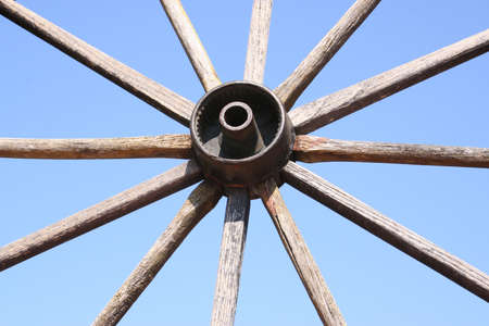 an old wagon wheel against the sky