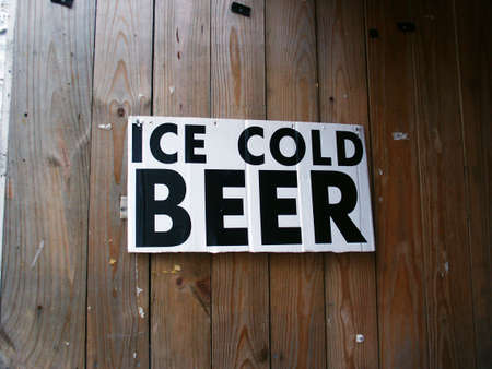 An Ice Cold Beer sign hanging on a wooden wall. Imagens