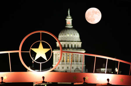 A shot of the star of Texas with the Texas State Capitol Building and the moon in the background. Imagens