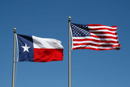 flagpoles: A Texas and US flag boldly flapping in the wind.