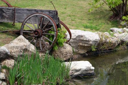 old wood farm wagon: An old broken down wagon near a pond