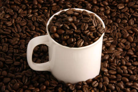 Coffee beans in a white coffee cup and all around it photo