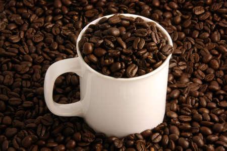 comida colombiana: Los granos de caf� blanco en una taza de caf� y todos a su alrededor