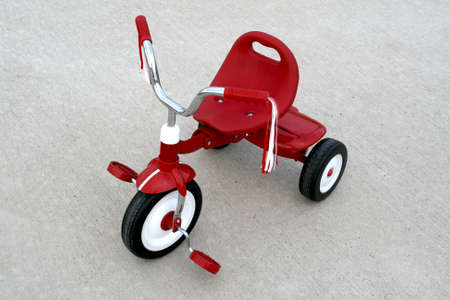 an empty red tricycle on a cement background