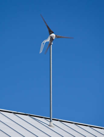 a small wind turbine windmill attached to a roof photo