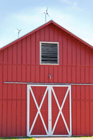 A red barn with solar and wind power generating electricity photo