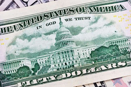 in god we trust: A stack of fifty 50 dollar bills fanned out with the back US Capitol showing on a white background