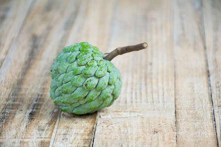 scaly custard apple: custard apple on a wooden floor. Stock Photo