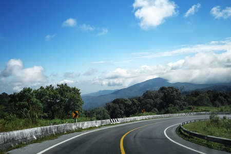 The steep curve descending from the mountain top overlooking the sky and white clouds, and on either side of the road is a deep abyss Stockfoto