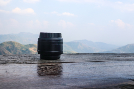 50mm lens placed on a wooden floor and a mountain background
