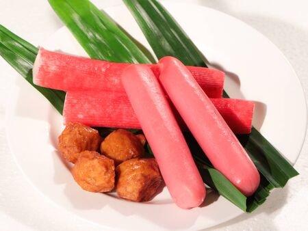 Meatballs with hot dogs and leaves placed on a white plate 写真素材