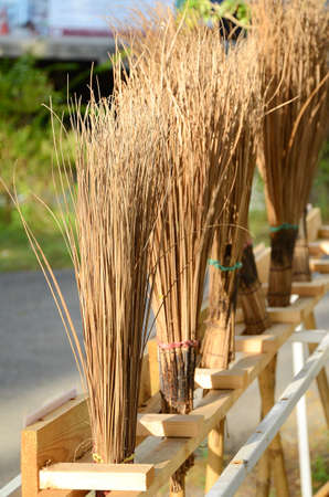 Row of big broom made from stems of coconut leaves  photo