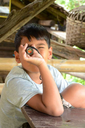 Asian boy playing with his monocular  photo