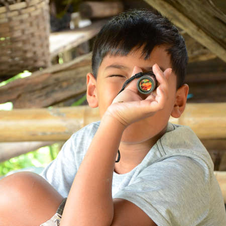 monocular: Asian boy playing with his monocular