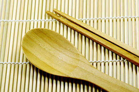 Teak wood kitchenware on bamboo mat background  photo