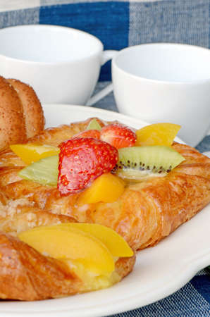 Afternoon snack serving with bread, waffle and Danish pastry topping with strawberry, kiwi and peach