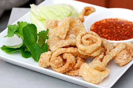 Pork snack, pork rind, pork scratching or pork crackling appetizers served with fresh vegetable and hot and spicy dipping sauce  Stock Photo