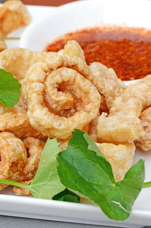 chicharon:  Pork snack, pork rind, pork scratching or pork crackling appetizers served with fresh vegetable and hot and spicy dipping sauce  Stock Photo
