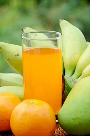 Bananas, mango, oranges and fresh orange juice from organic orchard in closed-up with natural green background  photo