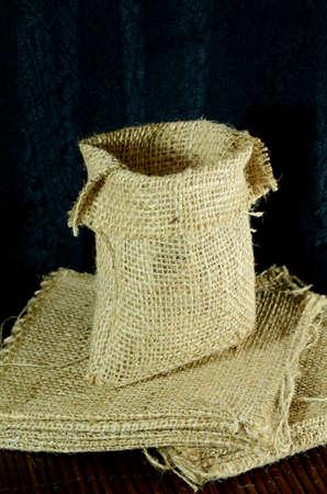 gunny: Heap of Empty Burlap Sack on Dark Background
