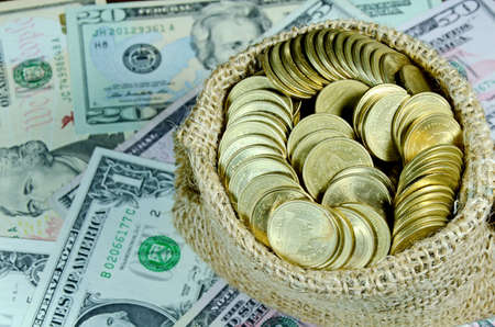 Gold Coins in Burlap Sack with Dollar Banknotes Background photo
