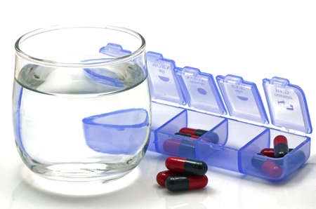 over lab: Oral medication red and black capsules in separated unit-dose box on white