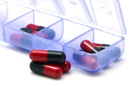 over the counter: Oral medication red and black capsules in separated unit-dose box on white