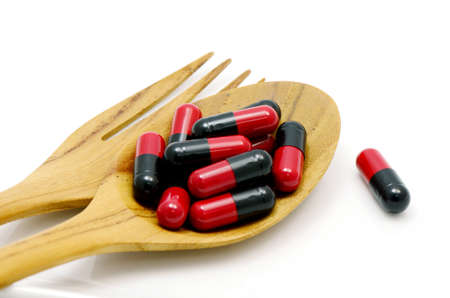 over the counter: Oral medication red and black capsules in a table spoon on white
