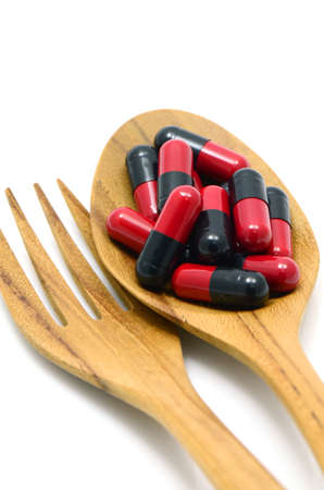 over lab: Oral medication red and black capsules in a table spoon on white