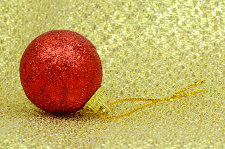 Red Decorating Ball on Golden Background Texture  photo