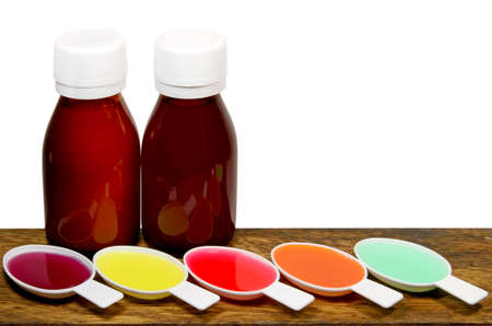 Syrup Medication Bottles and Medicine Spoons Isolated on White Background. photo