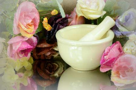 medical preparation: Porcelain herbal medicine grinder on floral background.