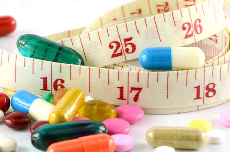drug therapy: Medicine and Tape Measure on White Background in Waistline and Weight Control Concept. Stock Photo
