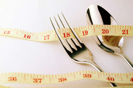 Tape Measure, Fork and Spoon in Waistline and Weight Control Concept by Diet Control. Stock Photo
