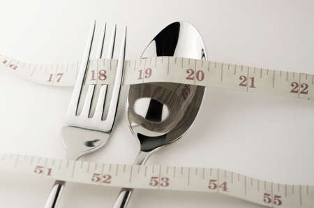 circumference: Tape Measure, Fork and Spoon in Waistline and Weight Control Concept by Diet Control. Stock Photo