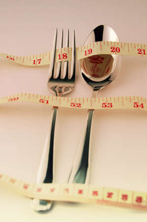 weight control: Tape Measure, Fork and Spoon in Waistline and Weight Control Concept by Diet Control. Stock Photo