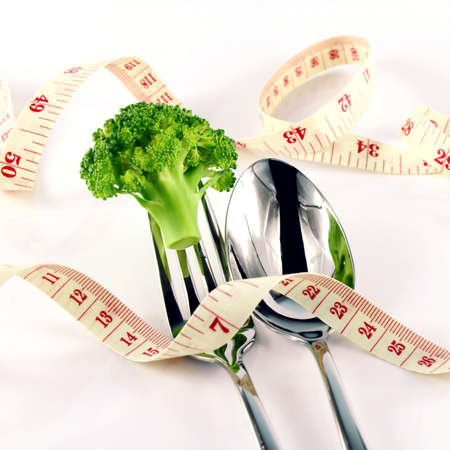 weight control: Broccoli, Tape Measure, Fork and Spoon in Waistline and Weight Control Concept by Diet Control. Stock Photo