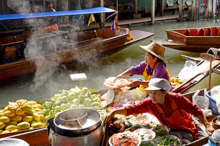 ratchaburi: RATCHABURI, THAILAND - MARCH 22: Local peoples sell fruits, food and souvenirs at famous tourist attraction Damnoensaduak floating market on March 22, 2015 in Ratchaburi, Thailand.