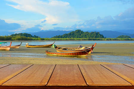 Outdoor Picnic Background with Wooden Table in Afternoon Light with Landed Folk Fishing Boat at Bang Ben Beach in Ranong, Thailand. photo