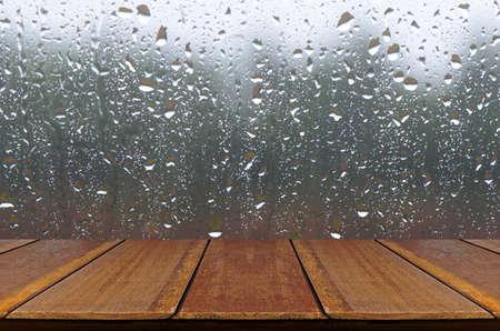 Gotas de lluvia en la ventana de fondo de cristal con la tabla de madera.